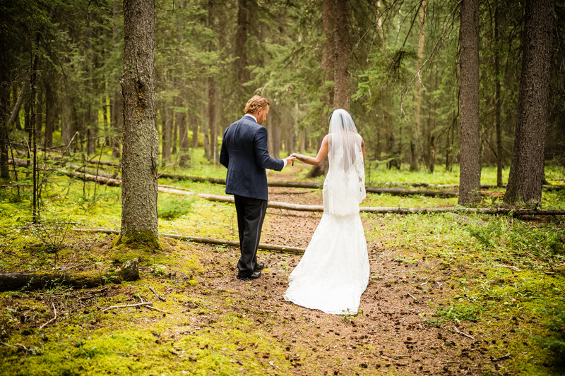 Bride + Groom Walking in Lush Woods Banff National Park