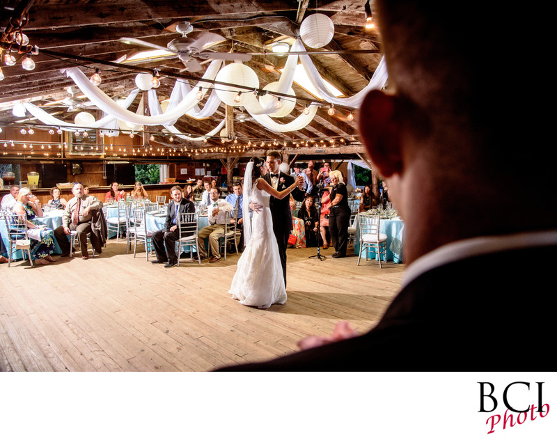 A groomsman looks on as the bride and groom first dance