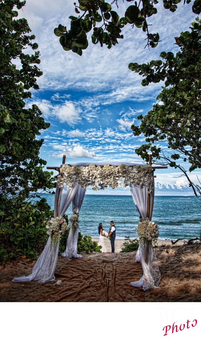 Bride and Groom portrait on the beach seen through the wedding canopy arch.