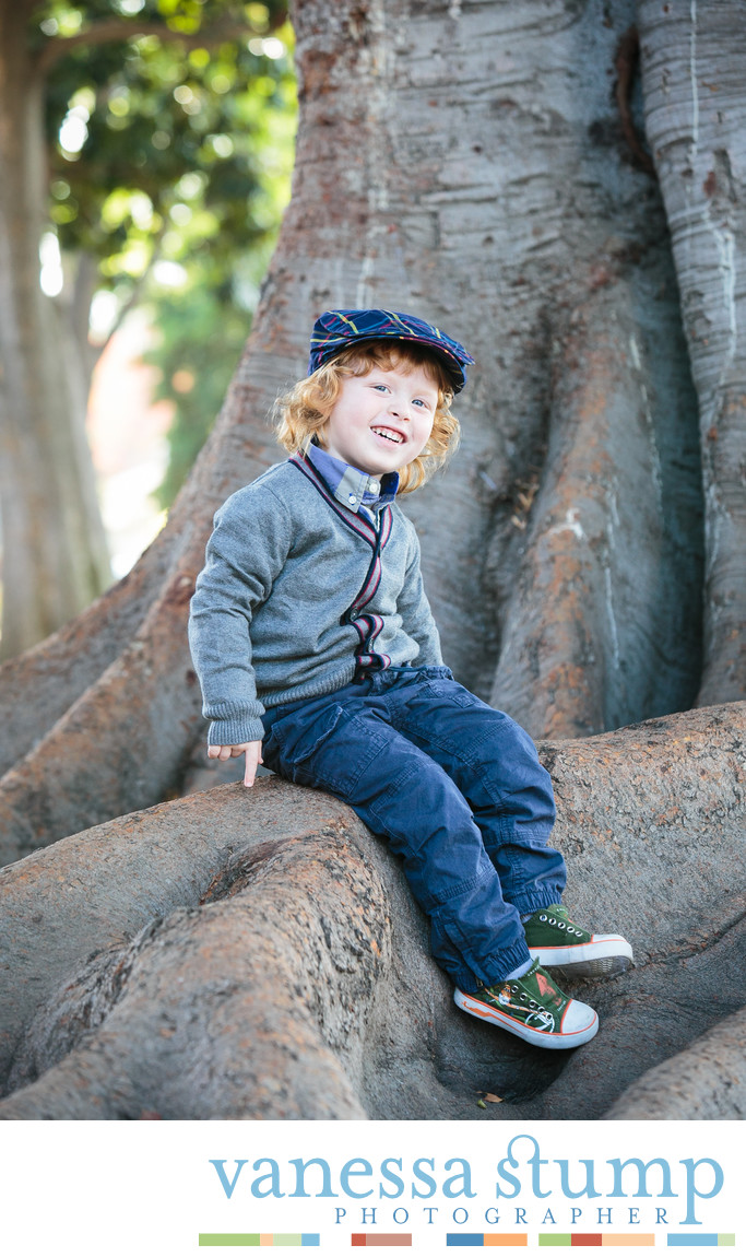 Portrait of cute young boy in newsboy cap sitting on a tree