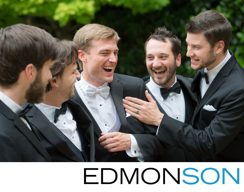 Groomsmen Laughing With Groom On Wedding Day Outdoors
