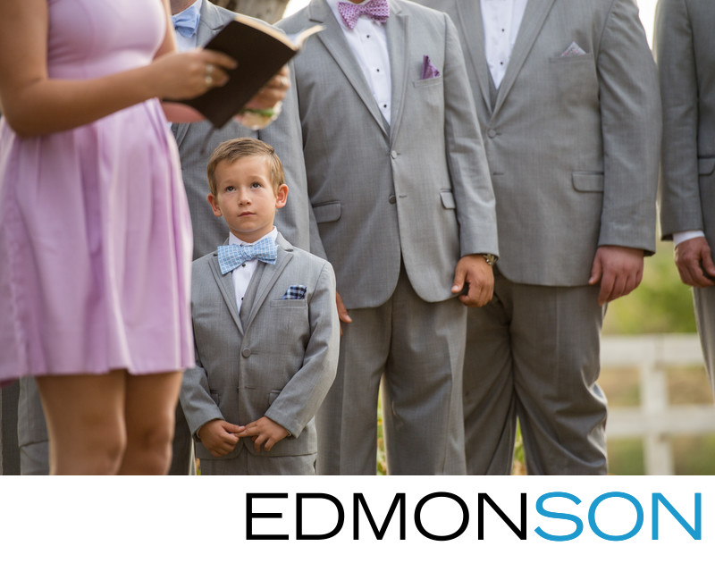 Cute Ring Bearer Holds His Hands Listening To Reader
