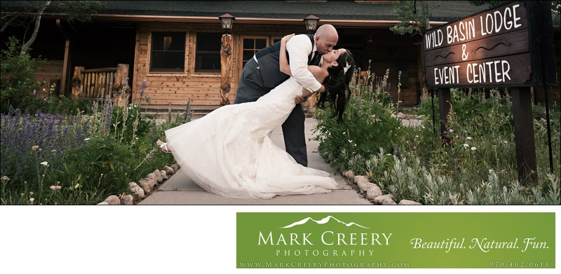Groom dipping & kissing bride in front of Wild Basin Lodge