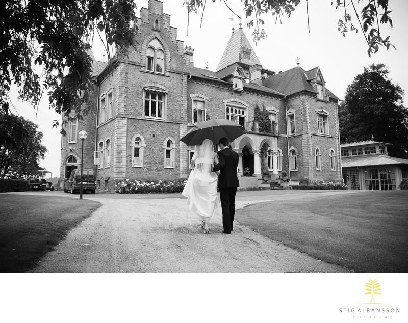 Svartvit bild på brudpar med paraply på Thorskogs slott