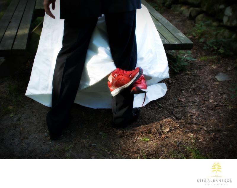 Röda gympaskor och vit brudklänning omfamnar brudgum