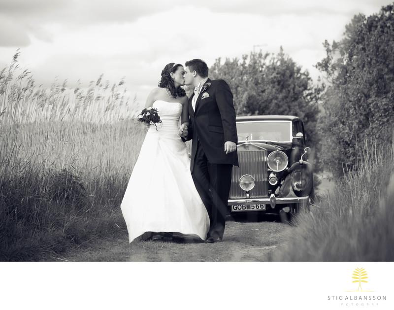 Brudpar kyss framför bil och vass Stora Holms säteri