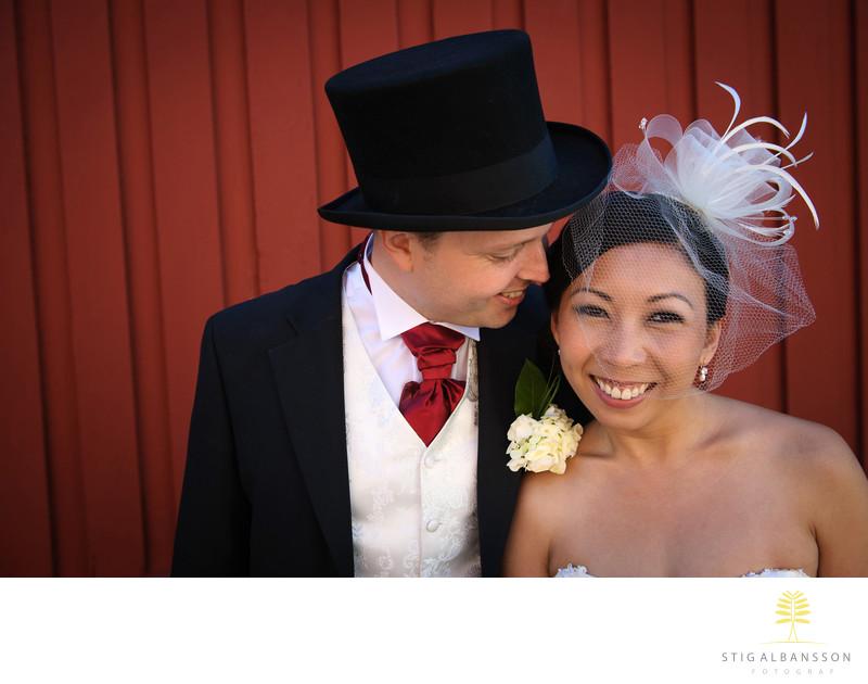 Glad brud och brudgum vid röd vägg S:t Birgittas kapell