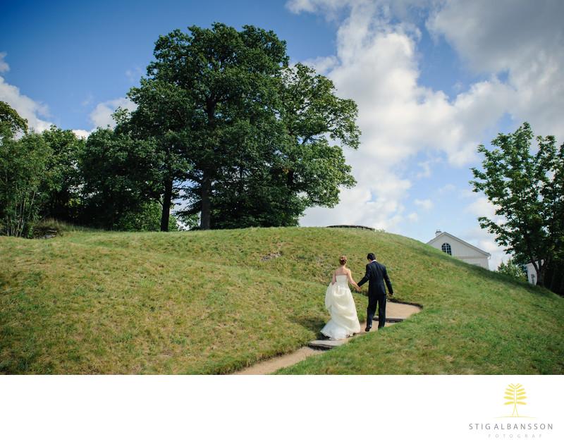 Brudpar går stigen uppför kulle invid Gunnebo slott