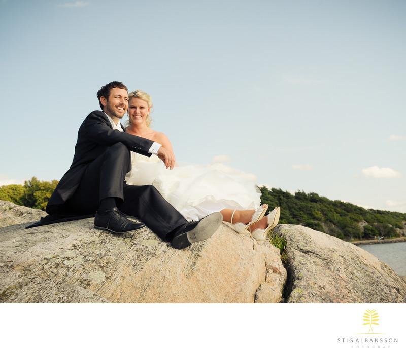 Brudpar sitter på klippa vid havet vid Tjolöholms slott
