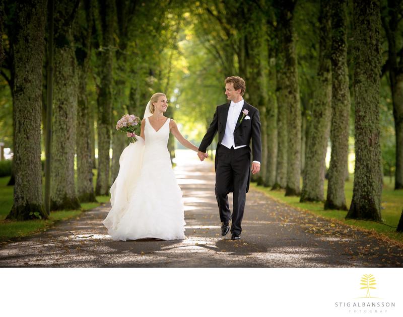 Brudpar promenerar i allé på Bjertorps slott