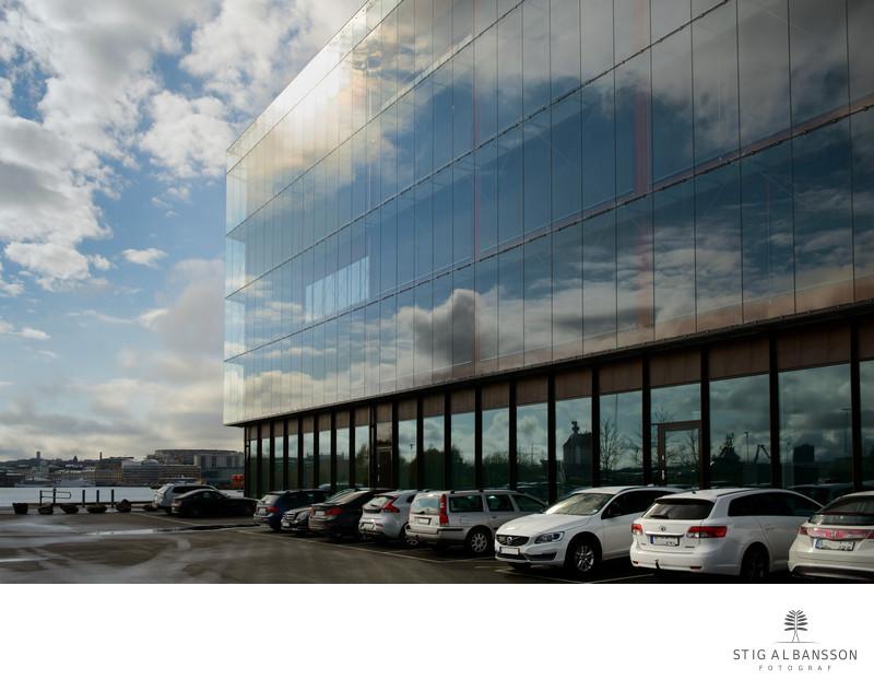 Fasad Semcon med bilar och spegling med moln - himmel