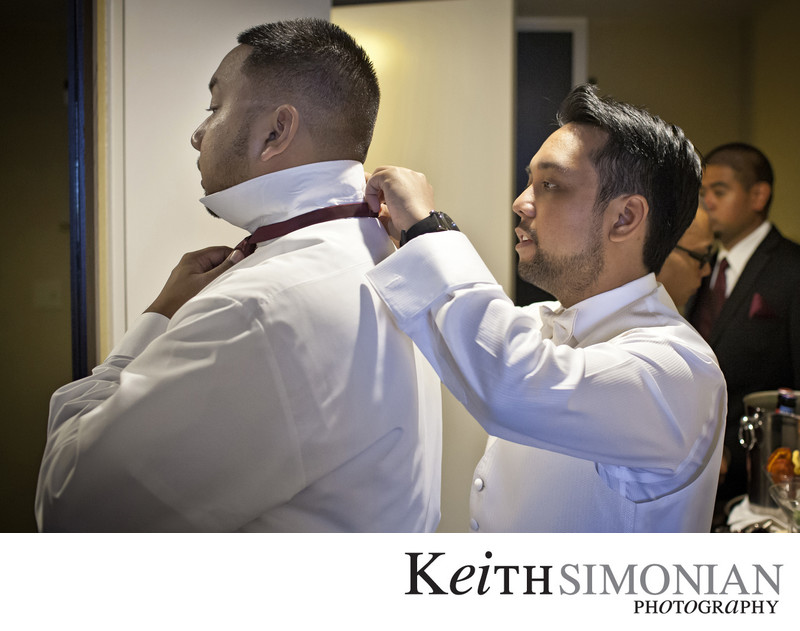 Groom helping groomsmen put on tie
