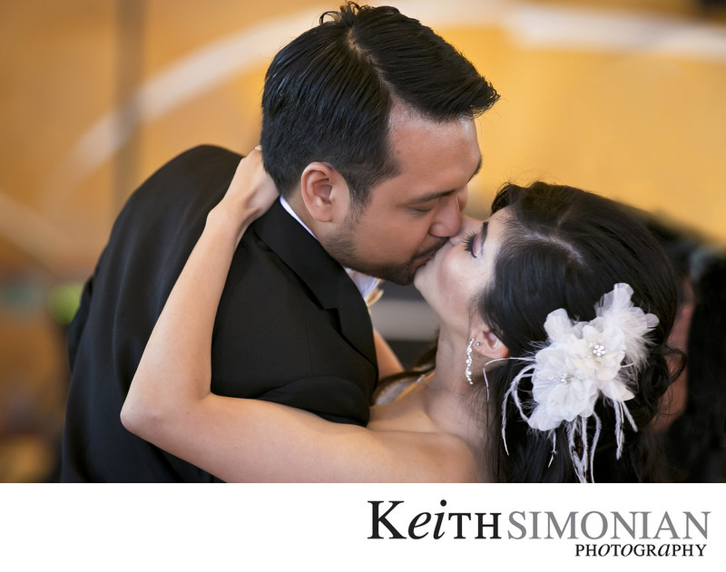 Groom kisses the bride as he dips her while dancing