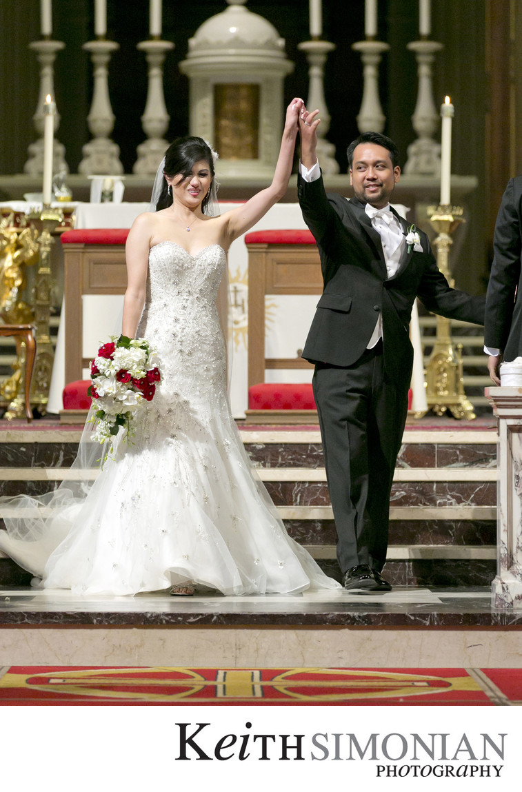 Bride and groom raises arms to celebrate their wedding