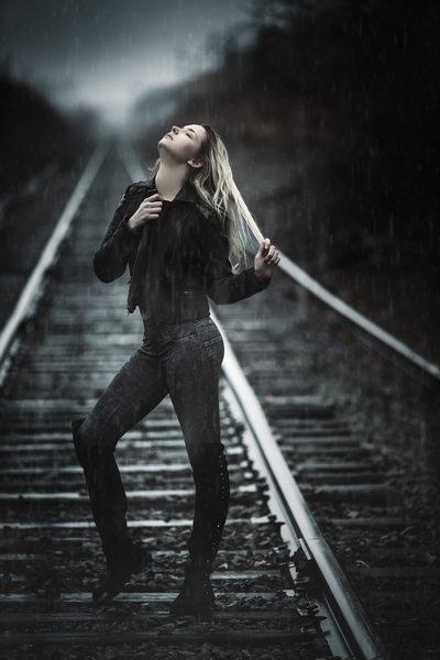 Woman in rain on railroad tracks