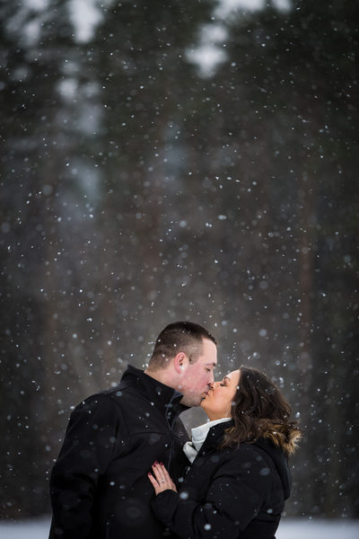 Engaged couple kissing in the snow