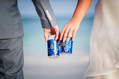 Bride and Groom Holding Beers on a Beach