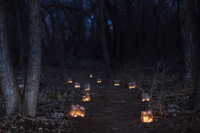 Candles along the path at sunrise in the bosque