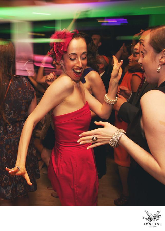 dancing wedding guest with sweet fascinator