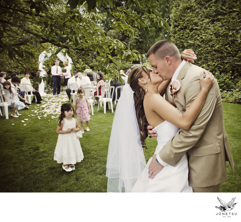 Backyard candid wedding kiss in West Vancouver