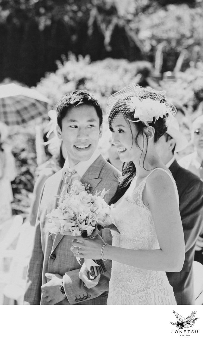 Groom steals a glance at his bride at garden ceremony