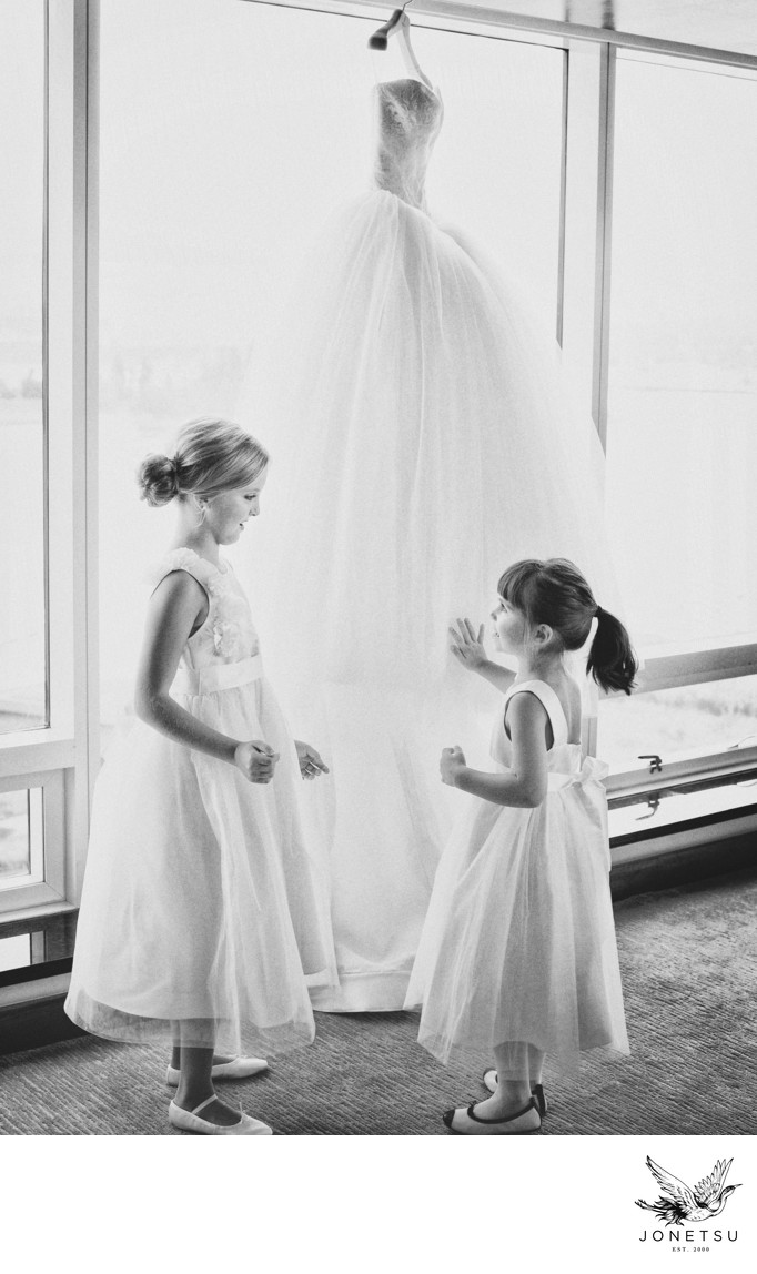 Flower girls touch the bride's Vera Wang gown