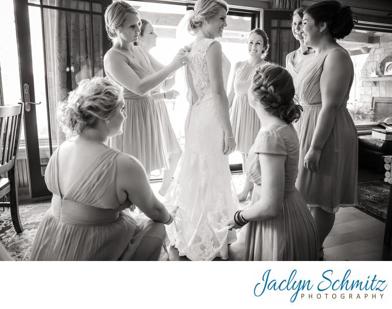 bridesmaids help bride put on dress