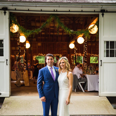 Bride and groom in front of barn West Mountain Inn
