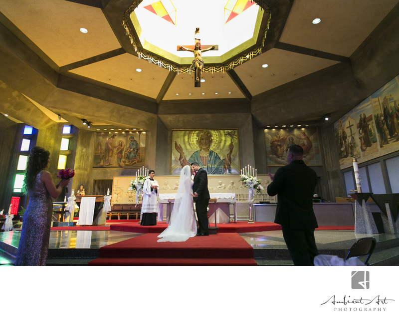 Bride and groom kiss at their Catholic Wedding in Fresno, CA