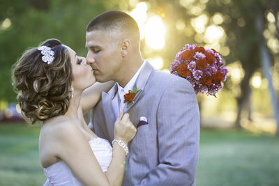 Bride and groom kissing with the bouquet. Clovis, CA
