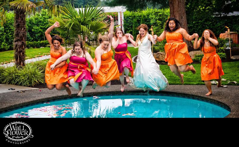 Bride and bridesmaids jump into pool — panorama crop
