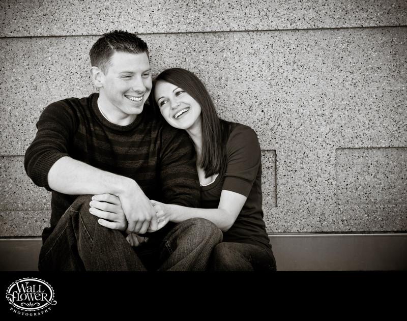 Engagement portrait sitting against concrete wall