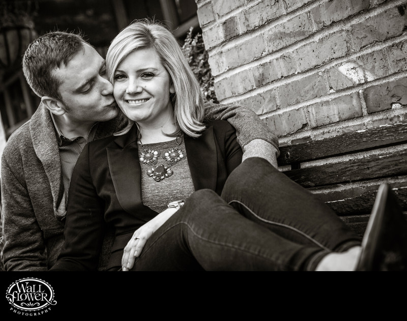 Engagement portrait of couple on bench in Post Alley