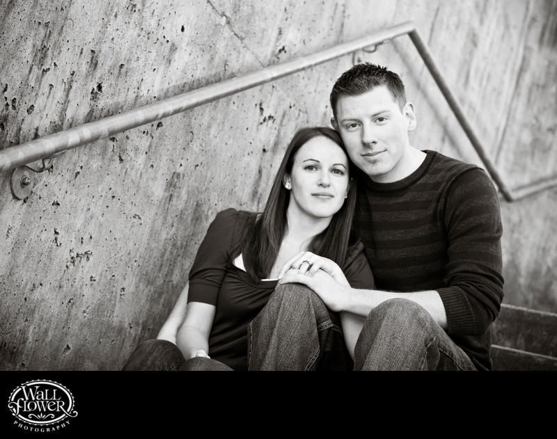 Engagement portrait on concrete steps with zig-zag rail