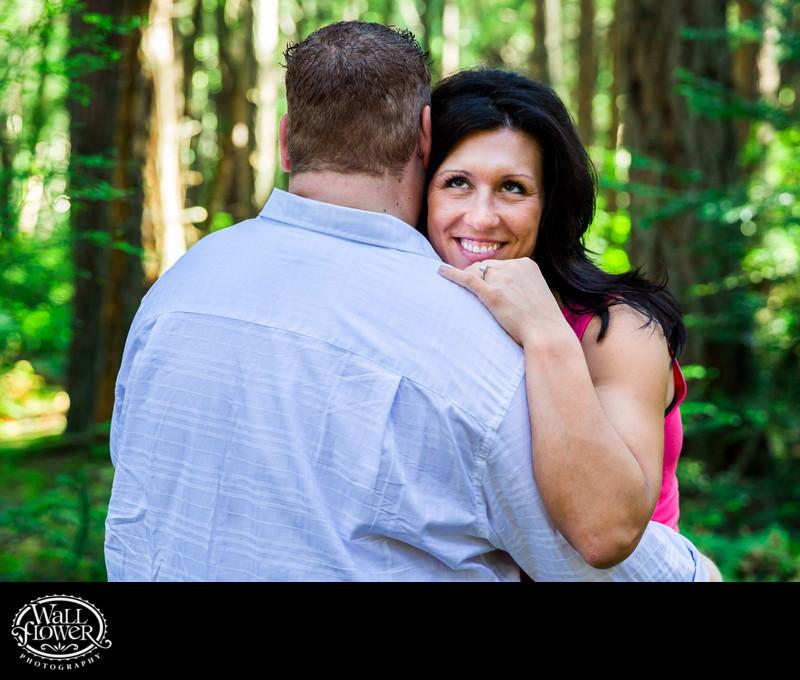 Engagement portrait smiling over his shoulder in forest