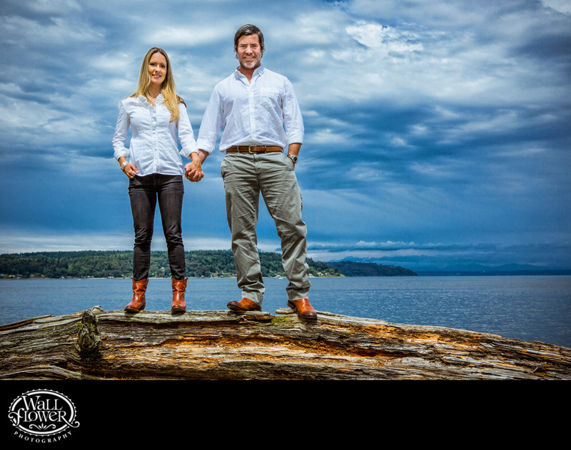 Engagement portrait standing on driftwood log at Owen Beach