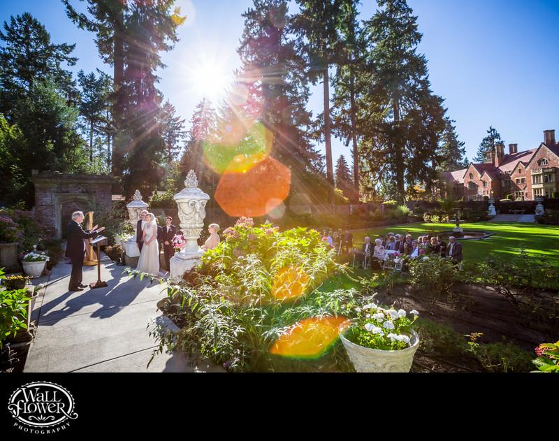 Wedding ceremony sun flare in Thornewood Castle garden