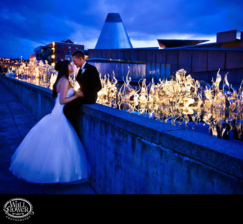 Bride and groom at dusk by glowing Museum of Glass art