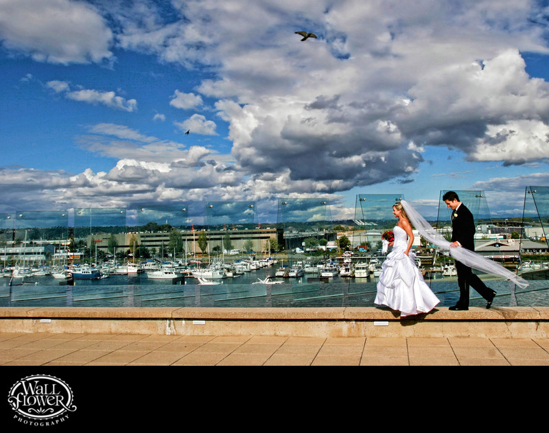 Bride and groom walk along Museum of Glass pool