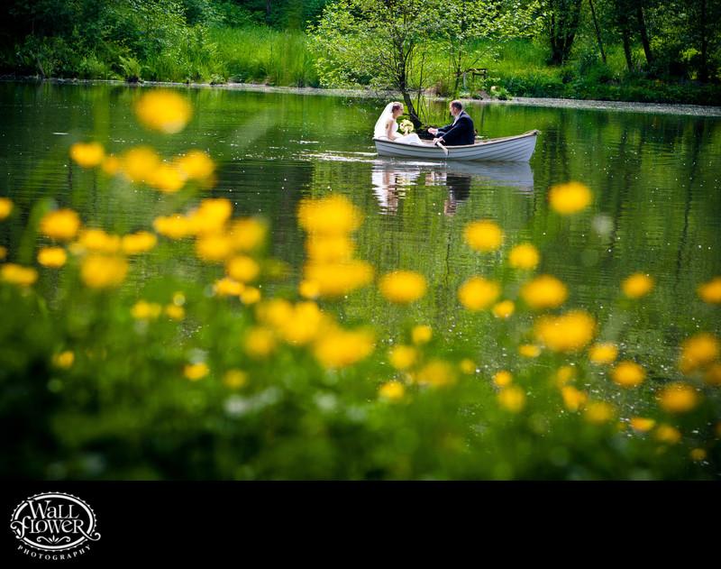 Bride and groom in rowboat on Sanders Estate pond