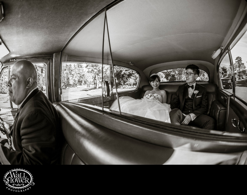 Fisheye photo of bride and groom in back of antique car