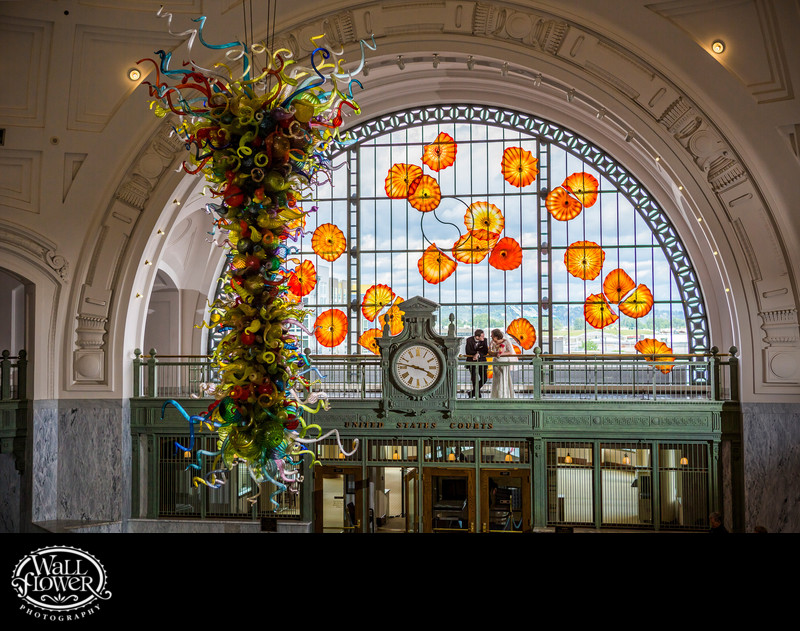 Bride and groom around Chihuly art at Union Station