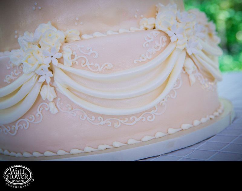 Detail of white icing on pink wedding cake