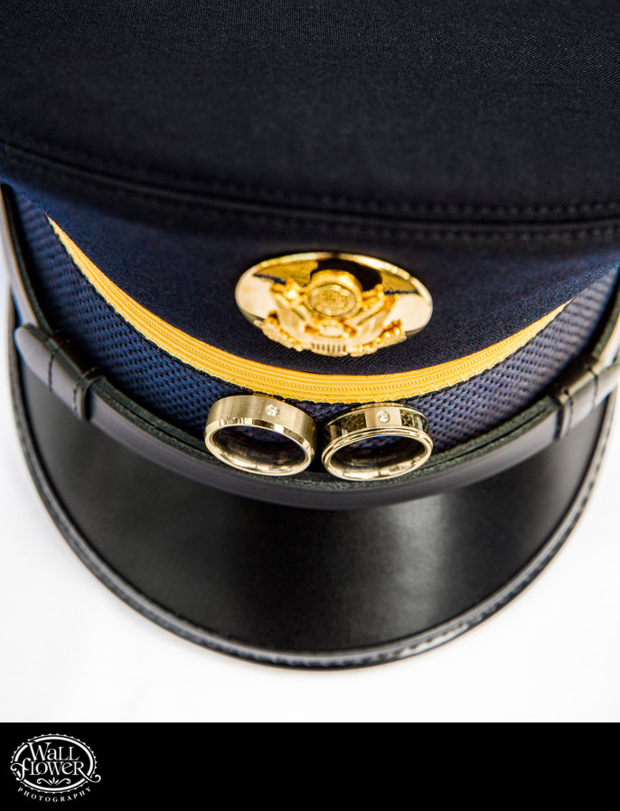 Detail of weddings rings of two grooms on Army hat band