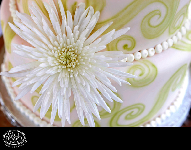 Detail of dahlia on white wedding cake with green curls