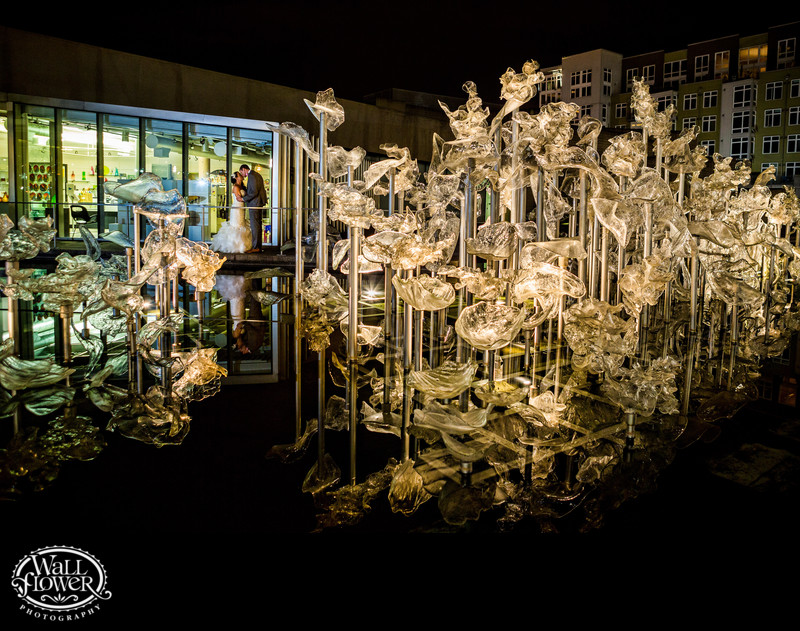Wedding night kiss near glowing art at Museum of Glass