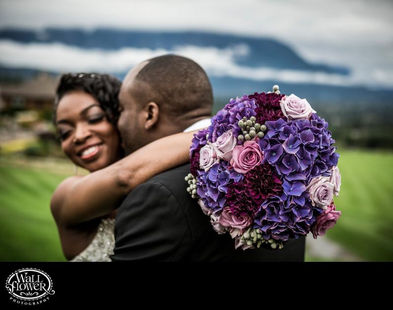 Toned detail photo of smiling bride's purple bouquet