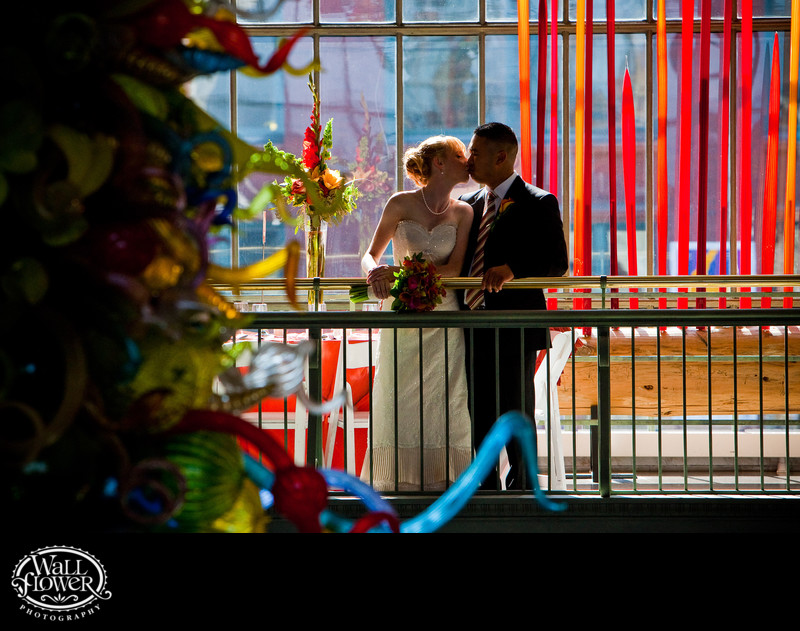 Bride and groom kiss by Chihuly glass in Union Station
