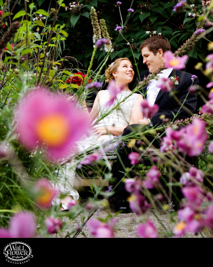 Bride and groom sit among flowers at Lakewold Gardens