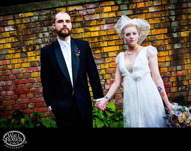 Bride and groom by brick wall at Thornewood Castle